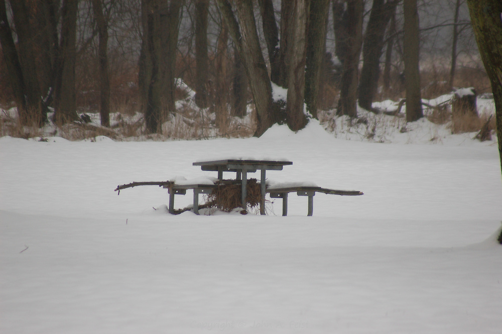 Snow and winter debris covering this picnic table along the D & R Canal in Hillsborough, NJ