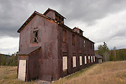 An old, rusted, metal building sits in an open field in rural Montana. Missoula Photographer, Missoula Photographers, Montana Pictures, Montana Photos, Photos of Montana