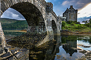Stone footbridge to Eilean Donan Castle, in Kintail National Scenic Area, Scotland, United Kingdom, Europe. This picturesque island stronghold sits where three sea lochs meet at the village of Dornie in the western Highlands (Loch Duich, Loch Long, and Loch Alsh). Since restoration of the 1200s castle in the early 1900s, a footbridge connects the island to the mainland. The island is named after Donnán of Eigg, a Celtic saint martyred in 617. The castle was founded in the 1200s and became a stronghold of the Clan Mackenzie and their allies the Clan Macrae. In the early 1700s, the Mackenzies' involvement in the Jacobite rebellions led in 1719 to the castle's destruction by government ships. Lieutenant-Colonel John Macrae-Gilstrap's 1920-32 reconstruction of the ruins made the present buildings.