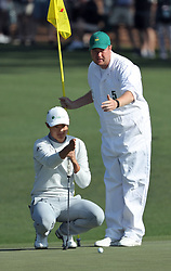 April 6, 2018 - Augusta, GA, USA - Haotong Li lines up his second hole putt with caddie Michael Burrow during the second round of the Masters Tournament at Augusta National Golf Club on Friday, April 6, 2018, in Augusta, Ga. (Credit Image: © Jason Getz/TNS via ZUMA Wire)