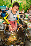 17 OCTOBER 2012 - BANGKOK, THAILAND:   A vendor cooks vegetarian noodles in the courtyard of Wat Mangkon Kamalawat, one of the largest Chinese shrines in Thailand, during the Vegetarian Festival in Bangkok. The Vegetarian Festival is celebrated throughout Thailand. It is the Thai version of the The Nine Emperor Gods Festival, a nine-day Taoist celebration celebrated in the 9th lunar month of the Chinese calendar. For nine days, those who are participating in the festival dress all in white and abstain from eating meat, poultry, seafood, and dairy products. Vendors and proprietors of restaurants indicate that vegetarian food is for sale at their establishments by putting a yellow flag out with Thai characters for meatless written on it in red.     PHOTO BY JACK KURTZ