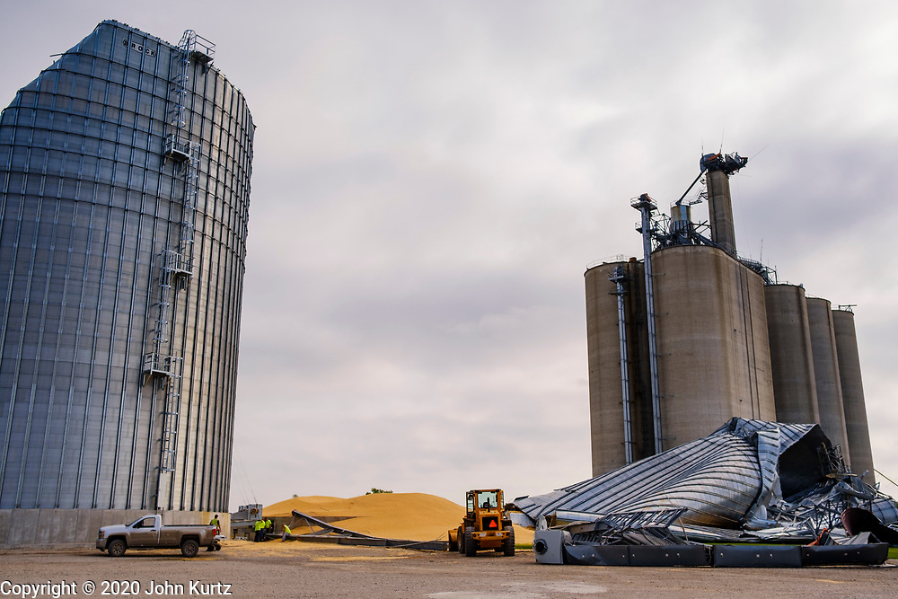 """12 AUGUST 2020 - SLATER, IOWA: Grain silos at the Heartland Cooperative in Slater were destroyed during the storm Monday. According to Iowa Governor Kim Reynolds, the storm damaged 10 million acres of corn and soybeans in Iowa, about 1 one-third of Iowa's 32 million acres of agricultural land. Justin Glisan, Iowa's state meteorologist, said the storm Monday, Aug. 10, lasted 14 hours and traveled 770 miles through the Midwest before losing strength in Ohio. The storm was a seldom seen """"derecho"""" that packed straight line winds of nearly 100MPH. The storm pummelled Midwestern states from Nebraska to Ohio.    PHOTO BY JACK KURTZ"""
