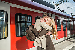 Young couple hugging at train station, Munich, Bavaria, Germany