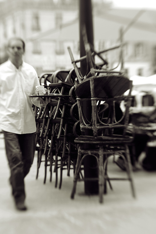 waiter in a foreign cafe carrying a tray with chairs piled on top of each ready to close.