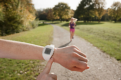 Women jogging in parkhand pointing on stop watch, Woerthsee, Bavaria, Germany