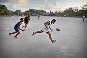 Young teenagers playing Aussie rule football...Nauru, officially the Republic of Nauru is an island nation in Micronesia in the South Pacific.  Nauru was declared independent in 1968 and it is the world's smallest independent republic, covering just 21square kilometers..Nauru is a phosphate rock island and its economy depends almost entirely on the phosphate deposits that originate from the droppings of sea birds. Following its exploitation it briefly boasted the highest per-capita income enjoyed by any sovereign state in the world during the late 1960s and early 1970s..In the 1990s, when the phosphate reserves were partly exhausted the government resorted to unusual measures. Nauru briefly became a tax haven and illegal money laundering centre. From 2001 to 2008, it accepted aid from the Australian government in exchange for housing a Nauru detention centre, with refugees from various countries including Afghanistan and Iraq..Most necessities are imported on the island..Nauru has parliamentary system of government. It had 17 changes of administration between 1989 and 2003. In December 2007, former weight lifting medallist Marcus Stephen became the President.