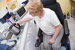 Female wheelchair user filling a kettle with water in her nonadapted kitchen,
