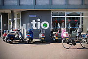 in Utrecht staan voor het gebouw van de TIO, een particuliere hbo en mbo opleiding in hotellerie, eventmanagement, toerisme en business scooters en een fiets. <br /> <br /> In Utrecht scooters and bicycles parked in front of the building of the TIO, a private college and vocational training in hospitality industry, event management, tourism and business.