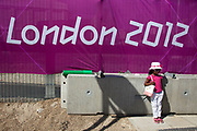 Area around Stratford in East London, home to the 2012 Olympic Games. Aa an event goes on behind the London 2012 sign, a little girl has her photo taken.