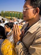 """02 JANUARY 2015 - KHLONG LUANG, PATHUM THANI, THAILAND: A man prays at Wat Phra Dhammakaya at the start of the 4th annual Dhammachai Dhutanaga (a dhutanga is a """"wandering"""" and translated as pilgrimage). More than 1,100 monks are participating in a 450 kilometer (280 miles) long pilgrimage, which is going through six provinces in central Thailand. The purpose of the pilgrimage is to pay homage to the Buddha, preserve Buddhist culture, welcome the new year, and """"develop virtuous Buddhist youth leaders."""" Wat Phra Dhammakaya is the largest Buddhist temple in Thailand and the center of the Dhammakaya movement, a Buddhist sect founded in the 1970s.   PHOTO BY JACK KURTZ"""