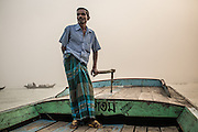 A boat driver steers his vessel early in the morning near Barisal, Bangladesh.
