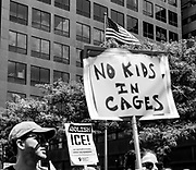 Signs underneath a flag of the USA during the Families belong together march.