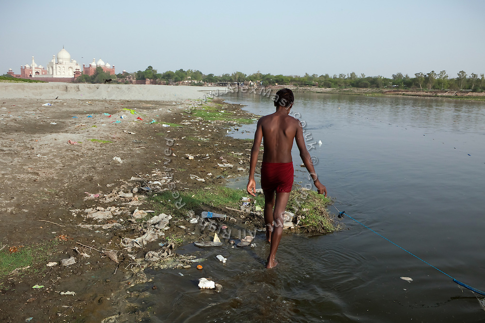 A boy is fishing on the heavily polluted and semi-dry Yamuna River, across a view of the Taj Mahal, in Agra.