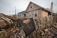 Union Beach NJ, November 16, A Jersey Shore rock concert  t-shirt on a fence behind a home destroyed by superstorm Sandy's surge, that damaged over 200 homes in Union Beach alone. Hurricane Sandy's strength is being blamed on climate change by many scientists.