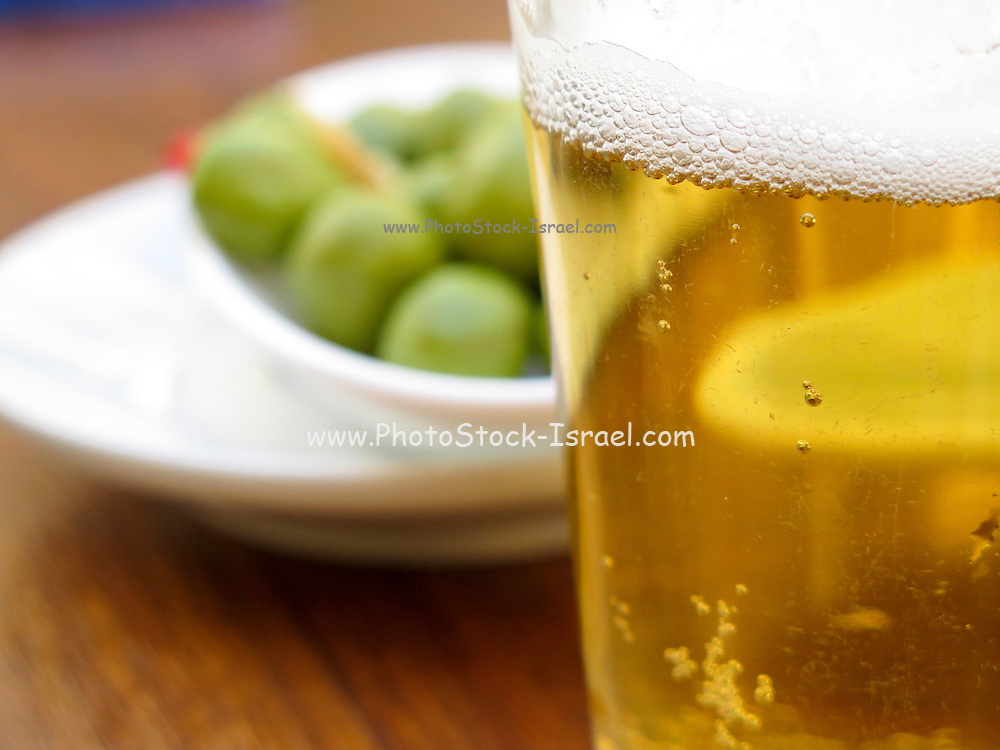 Pint of beer served with olives