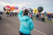 Hannah Gillreath watches balloons inflate on the field at the AARP Block Party at the Albuquerque International Balloon Fiesta in Albuquerque New Mexico USA on Oct. 7th, 2018.