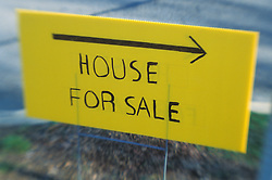 Hand made yellow house for sale sign in front yard. CONCEPT STOCK PHOTOS