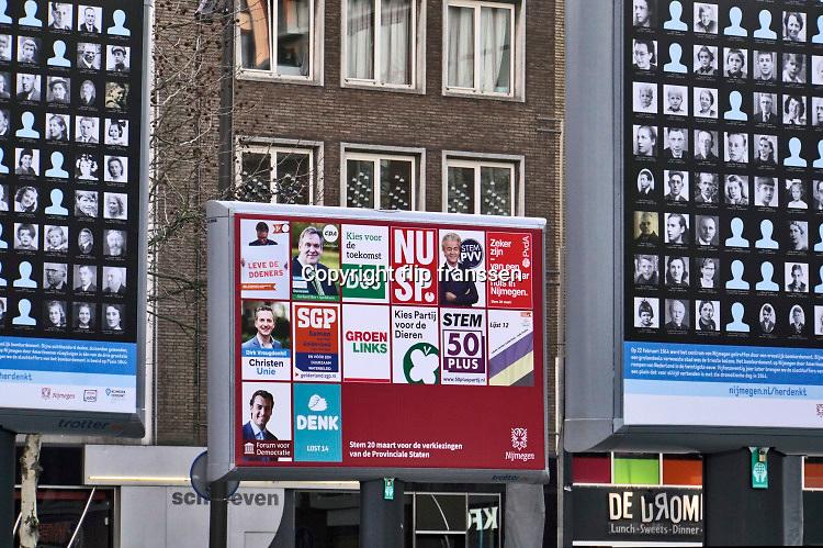 Nederland, Nijmegen, 15-2-2019Op Plein44 staan grote borden met daarop de portretjes van slachtoffers van het vergissingsbombardement op de stad, 75 jaar geleden in 1944. Bijna 800 doden. Op 22 februari wordt dit uitrgebreid herdacht. Tussen deze borden is het verkiezingsbord te zien waarop affiches voor de komend eprovinciale verkiezingen zijn aangebracht. Een opvallende combinatie.Foto: Flip Franssen