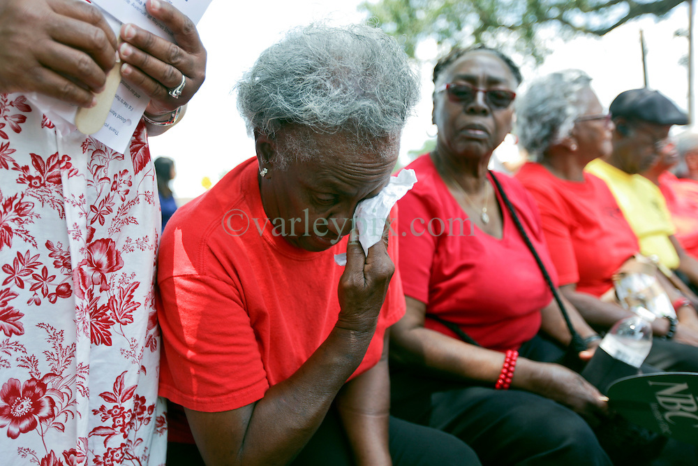 29 August 2015. Lower 9th Ward, New Orleans, Louisiana.<br /> Hurricane Katrina 10th anniversary memorials.  <br /> An elderly Katrina survivor wipes a tear from her eye during the memorial service. <br /> Photo credit©; Charlie Varley/varleypix.com.