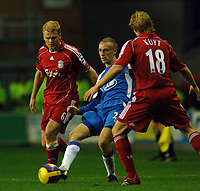Photo: Paul Greenwood.<br />Wigan Athletic v Liverpool. The Barclays Premiership. 02/12/2006. Wigan substitute Dvid Cotterill (centre) takes on Liverpools John Arne Riise, left and Dirk Kuyt.