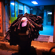 """A worker carries a pile of jeans in Zhongshan city, China, from a factory with Chinese good-luck banners on the gate.  .This picture is part of a photo and text story on blue jeans production in China by Justin Jin. .China, the """"factory of the world"""", is now also the major producer for blue jeans. To meet production demand, thousands of workers sweat through the night scrubbing, spraying and tearing trousers to create their rugged look. .At dawn, workers bundle the garment off to another factory for packaging and shipping around the world..The workers are among the 200 million migrant labourers criss-crossing China.looking for a better life, at the same time building their country into a.mighty industrial power."""