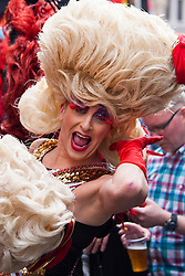 London, June 28th 2014. A drag queen preens for the camera as thousands of London's LGBT community and their supporter throw a vast party in Soho.