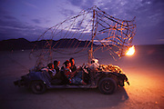 A flame breathing buffalo art car prowls the desert at dusk at the Burning Man Festival. Burning Man is a performance art festival known for art, drugs and sex. It takes place annually in the Black Rock Desert near Gerlach, Nevada, USA.