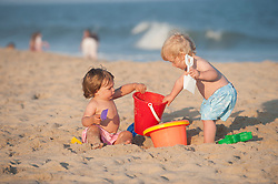 two little boys playing on the beach with beach pails in the sand at the ocean in The Hamptons