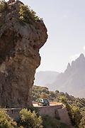 Car on road on rocky cliff, Calanches de Piana, Corsica, France