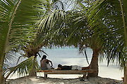 Belize, Central America - Family takes some time off on a bench watching the sea under some palm trees on Caye Caulker