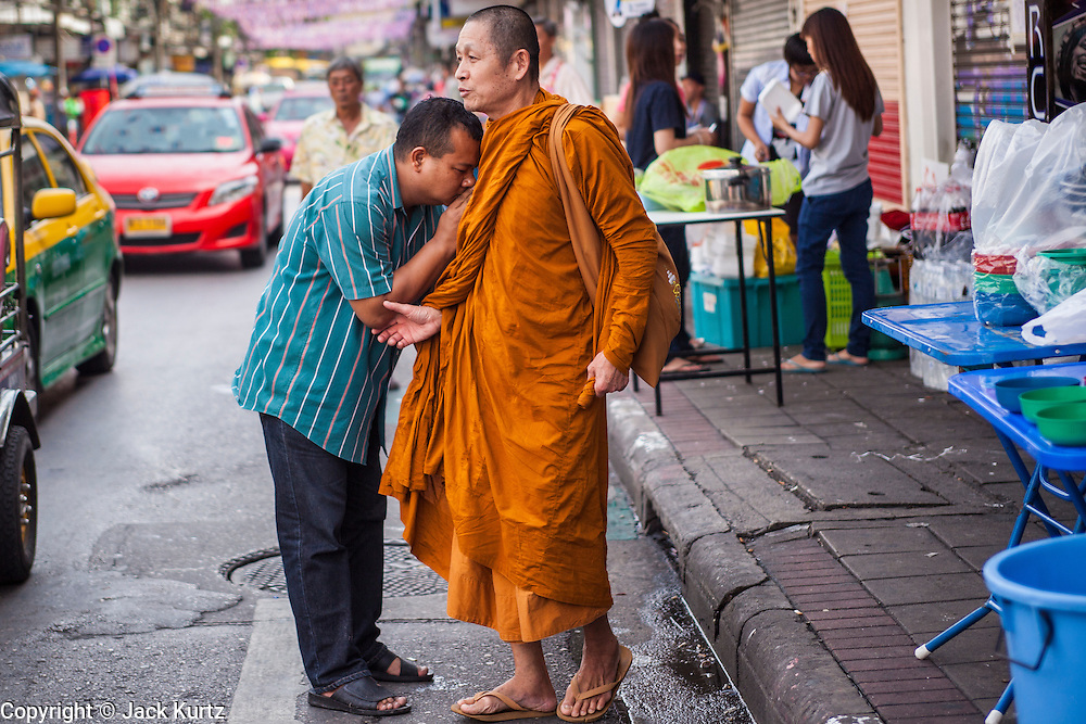 13 APRIL 2013 - BANGKOK, THAILAND:  A man stops a Buddhist monk and offers Songkran prayers in Bangkok. Songkran is the traditional Thai New Year's Festival. It is held April 13-16. Many Thais mark the holiday by going to temples and making merit by giving extra alms to monks or offering extra prayers. They also mark Songkran with joyous water fights. Songkran has been a national holiday since 1940, when Thailand moved the first day of the year to January 1.   PHOTO BY JACK KURTZ
