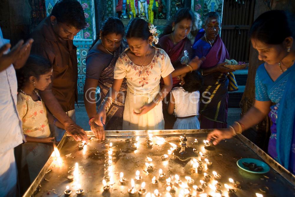 Devotees light oil lamps in the Murugan temple, Swamimalai, India.