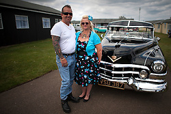 © London News Pictures. 11/05/2013. Hemsby, UK.  Husband and wife Ashley and Mandy Geater from Ipswich pose with their classic American car at  the Hemsby Rock 'n' Roll Weekender  in Hemsby, Norfolk. Twice a year rock and roll enthusiasts gather in the grounds of the Authentic 1950s Seacroft Holiday Site to re-live the 50's by dressing in keeping with the period and listening to live bands playing jive, hop, bop and Rock 'n' Roll. Photo credit: Ben Cawthra/LNP