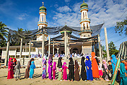 26 OCTOBER 2012 - PULASAIZ, NARATHIWAT, THAILAND: Children line up in front of the mosque for their Eid al-Adha gifts in the villiage Pulasaiz, in the province of Narathiwat, Thailand. Eid al-Adha, also called Feast of the Sacrifice, is an important religious holiday celebrated by Muslims worldwide to honor the willingness of the prophet Ibrahim (Abraham) to sacrifice his firstborn son Ishmael as an act of submission to God, and his son's acceptance of the sacrifice before God intervened to provide Abraham with a ram to sacrifice instead. In 2012 Eid al-Adha was celebrated Oct 25 - 26.     PHOTO BY JACK KURTZ