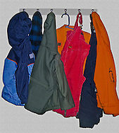 winter toddler's clothes hanging on wall hooks