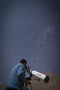 Man using telescope, looking on night sky, Elqui Valley, Chile