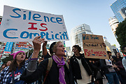 """A woman holds a sign that reads, """"Silence is Complicity"""" at the Vote Out the Scandal rally at Hachiko Square, Shibuya, Tokyo, Japan. Sunday November 5th 2017. Timed to coincide with President Trumps visit to Japan, About 120 Americans living in Japan and some local Japanese  protested together from 2pm to 4pm to encourage US citizens to register to vote in future elections and call on the US government to honour it responsibilities to the American people,."""