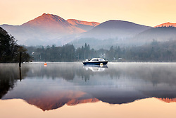 © Licensed to London News Pictures. 02/03/2021. Keswick UK. A boat & the mountains reflect into the calm water off Derwent Water at sunrise this morning in Cumbria. Photo credit: Andrew McCaren/LNP