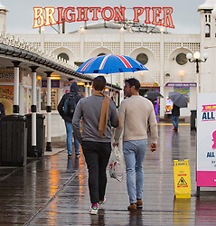 Brighton, UK. 04/11/2016, Members of the public shelter under their umbrellas in Brighton as rain and cold weather are hitting the seaside resort. Photo Credit: Hugo Michiels
