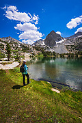 Hiker on the shore of Treasure Lake, John Muir Wilderness, Sierra Nevada Mountains, California USA