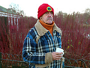 Ron Whittam, a member of the Serpentine Swimming Club, drinks a cup of tea after swimming on a cold Winter's day, Hyde Park, London, UK. The Serpentine Lake is situated in Hyde Park, London's largest central open space. The Serpentine Swimming Club was formed in 1864 'to promote the healthful habit of bathing in open water throughout the year'.  Its headquarters were beneath an old elm tree on the south side of the lake, a wooden bench for clothing being the only facility.  At this time London was undergoing rapid expansion and Hyde Park was now in the centre of a densely populated built up area and provided a place of relaxation to its urbanised masses. Now, the club has its own (somewhat spartan) changing facilities and members are  permitted by the Royal Parks to swim in the lake any morning before 09:30.  They race every Saturday morning throughout the year, regardless of the weather.