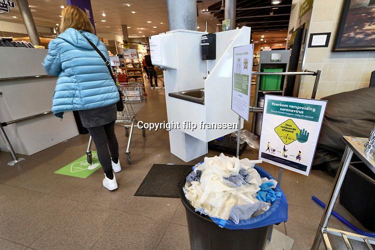 Nederland, Berg en Dal, 25-3-2020 In deze Plus supermarkt wordt klanten gevraagd om eerst hub handen te ontsmetten bij de ingang van de winkel . Er wordt handgel aangeboden en water en zeep om de ahnden te wassen . Sinds gisteren is er een strikt deurbeleid als gevolg van de afgekondigde maatregelen door de regering.  Er mogen nog maar een beperkt aantal mensen tegelijk in de winkel zijn. Klanten krijgen bij de ingang een doekje om  het handvat van het verplichte karretje te desinfecteren. Dit alles gebeurd ook om het eigen personeel te beschermen tegen het besmetten door klanten . Foto: Flip Franssen