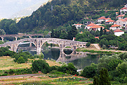 An old Roman stone bridge across the river Trebisnjica. Houses. Trebinje. Republika Srpska. Bosnia Herzegovina, Europe.