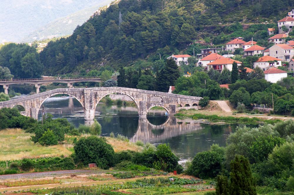 An old Roman stone bridge across the river Trebisnjica. Houses. Trebinje. Republika Srpska. Bosnia Herzegovina, Europe.