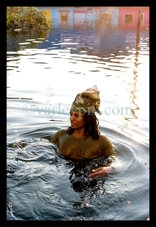 5th Sept, 2005. Hurricane Katrina aftermath. New Orleans. Derek Williams (32) swims through the murky water in Uptown as he and his family attempt to rescue their business.