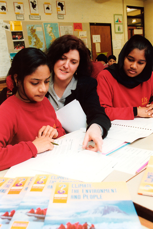 Geography teacher with pupils at secondary school London UK