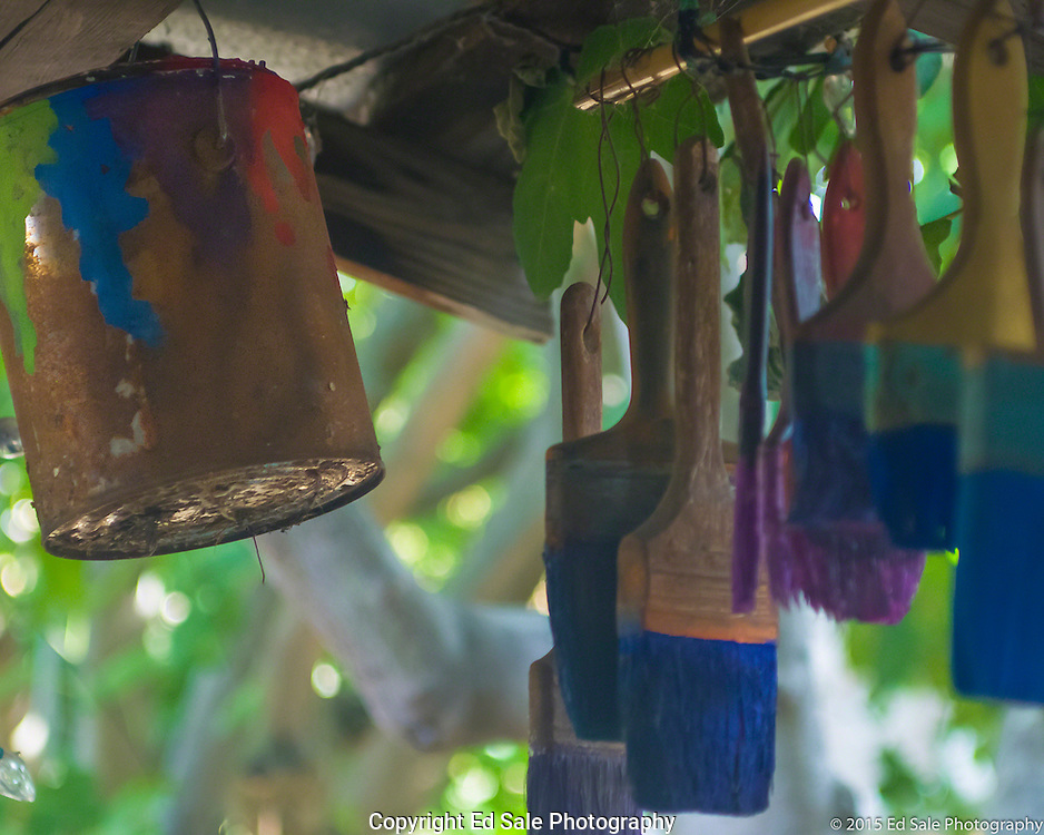 Old paint bucket and colorful brushes hang from the porch of The Art Shack in Locke, California