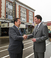 Mayor Ed Engler and Randy Eifert Vice Chair of the Belknap Economic Development Council BEDC shake hands on Main Street following the press conference announcing the purchase of the Colonial Theater in downtown Laconia.  (Karen Bobotas/for the Laconia Daily Sun)