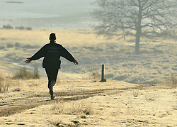 © Licensed to London News Pictures. 02/12/2012. Richmond, UK A jogger stretches her arms as she runs through the heavy frost. Deer, joggers and dog walkers wake up to a golden frosty morning in Richmond Park, Surrey, today 2nd December 2012. Photo credit : Stephen Simpson/LNP