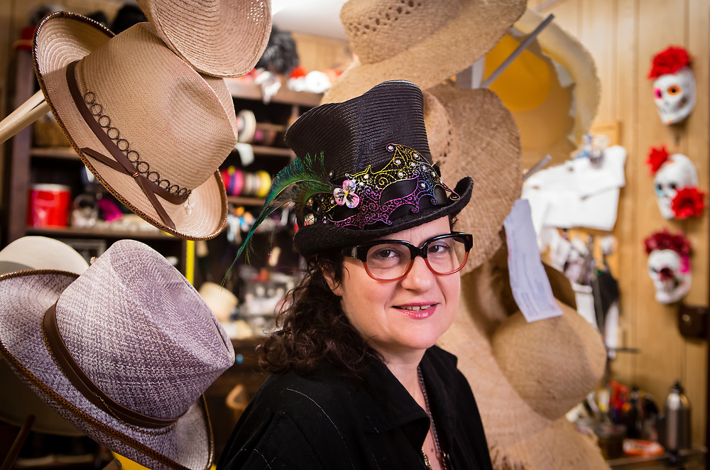 """Dina """"Cha Cha"""" Pisani wearing a decorated straw top hat, and surrounded by her creations, in her shop."""